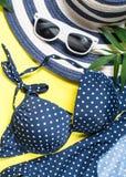 Набор ткани пляжа лета женщины - шляпа, купальник и солнечные очки на желтом взгляде сверху стоковое фото