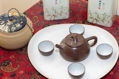 Набор чая глины Брауна китайский распространил вне на белой плите рядом с традиционным травяным чаем в глиняных горшках и жестяны стоковая фотография