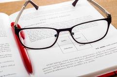 Наблюдайте стекла и красная ручка на открытых местах книги на деревянном столе stu Стоковое Фото