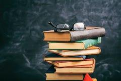 Наблюдайте стекла на винтажном стоге книг - предпосылке классн классного Стоковое Фото