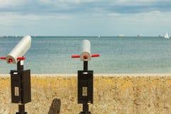 Наблюдая телескоп биноклей trought моря на пристани Стоковые Изображения RF