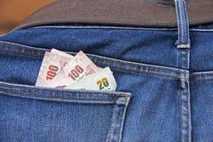 Навалите банкноты Таиланда позади карманн голубых джинсов Стоковое Изображение RF