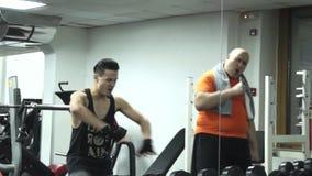 Наварный смешной человек и молодой красивый спортсмен танцуют в спортзале акции видеоматериалы