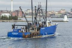 Наведение рыболовецкого судна промышленного рыболовства проходя маяк стоковые фото