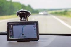 Навигатор расположен на ветровом стекле автомобиля показывая путь к водителю во время путешествия стоковое изображение rf