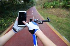 Навигатор gps пользы рук велосипедиста на smartphone Стоковое фото RF