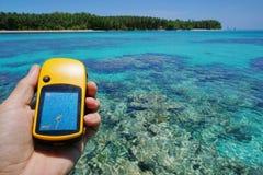 Навигатор GPS спутниковый в руке над тропическим морем Стоковое фото RF