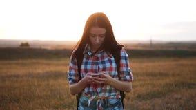 Навигация положения поиска wanderer девушки силуэта hiker битника идя на smartphone мобильного телефона для того чтобы найти прав сток-видео