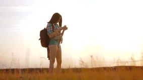 Навигация положения поиска wanderer девушки силуэта hiker битника на smartphone мобильного телефона для того чтобы найти правый п видеоматериал
