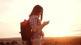 Навигация положения поиска wanderer девушки силуэта hiker битника на smartphone мобильного телефона для того чтобы найти правый п акции видеоматериалы