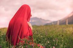 Нагая женщина в красном шарфе в поле на заходе солнца