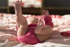 Нагие ноги младенца в створках Стоковая Фотография