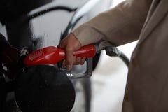 Нагнетая газ для того чтобы заполнить топливный бак на каникулы Стоковые Фотографии RF