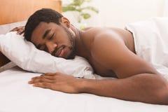 Нагой чернокожий человек спать в кровати дома стоковые изображения rf