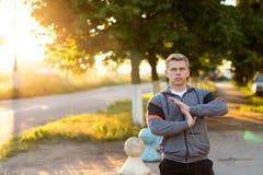 Нагревайте руки, молодой бегуна парня рано утром делая наушники Человек в парке слушает к музыке, a стоковое изображение