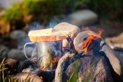 Нагревающ чашку чаю с сандвичем на лагерном костере внешнем Стоковое Фото