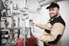 Нагревая контролер инженера или водопроводчика в котельной принимая отсчеты или регулировать метр стоковые изображения