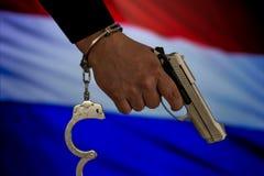 Надеванная наручники рука перед флагом страны стена тени пистолета удерживания руки фронта злодеяния принципиальной схемы кирпича стоковая фотография rf