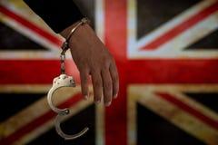 Надеванная наручники рука перед флагом страны стена тени пистолета удерживания руки фронта злодеяния принципиальной схемы кирпича стоковые фото