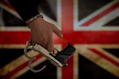 Надеванная наручники рука перед флагом страны стена тени пистолета удерживания руки фронта злодеяния принципиальной схемы кирпича стоковые изображения rf