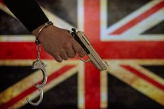 Надеванная наручники рука перед флагом страны стена тени пистолета удерживания руки фронта злодеяния принципиальной схемы кирпича стоковые изображения