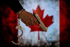 Надеванная наручники рука перед флагом страны стена тени пистолета удерживания руки фронта злодеяния принципиальной схемы кирпича стоковые фотографии rf