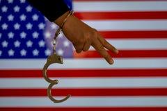Надеванная наручники рука перед флагом страны стена тени пистолета удерживания руки фронта злодеяния принципиальной схемы кирпича стоковое изображение rf