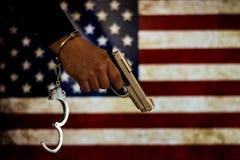 Надеванная наручники рука перед флагом страны стена тени пистолета удерживания руки фронта злодеяния принципиальной схемы кирпича стоковое фото rf