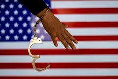 Надеванная наручники рука перед флагом страны стена тени пистолета удерживания руки фронта злодеяния принципиальной схемы кирпича стоковое изображение