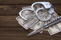Надеванные наручники доллары ножа и денег стоковое фото