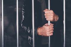 Надеванный наручники человек за барами тюрьмы Стоковая Фотография RF