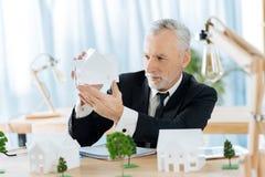Надежный агент недвижимости смотря миниатюру дома и думать стоковое изображение