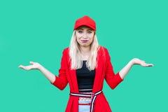наденьте меня знайте t Портрет смущенной красивой белокурой молодой женщины стиля хипстера в красных блузке и крышке, стоя с подн стоковое фото rf