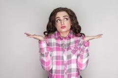 наденьте меня знайте t confused красивая девушка с розовой checkered рубашкой, стоковые изображения rf