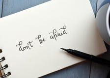НАДЕНЬТЕ ` T ИСПУГАННЫЕ рук-lettered в блокноте с ручкой щетки стоковые фото