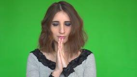 Надеющийся женщина держит руки совместно в моля жесте над зеленой предпосылкой акции видеоматериалы
