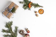 НАДЗЕМНАЯ ДЕРЕВЕНСКАЯ ДОМОДЕЛЬНАЯ ПРИСУТСТВУЮЩАЯ КОРОБКА рождество предпосылки орнаментирует белизну стоковое изображение