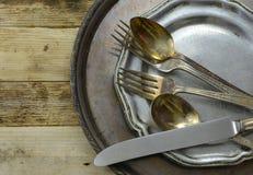 Надземная перспектива tarnished серебра покрыла плоские изделия и диск с worn блюдом певтера на деревенской предпосылке деревянно Стоковая Фотография RF