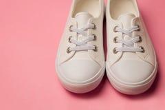 Надземная съемка белых женских тапок на предпосылке пастельного пинка Стоковые Изображения
