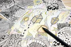 Надземное фото абстрактных картин doodle сделанных черной ручки вкладыша на деревянном столе Ходы ручки Doodle, illustr путать Стоковые Фотографии RF