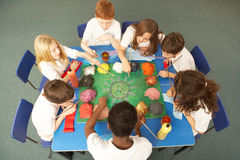 надземные ребенокы школьного возраста совместно осматривают работу стоковая фотография rf
