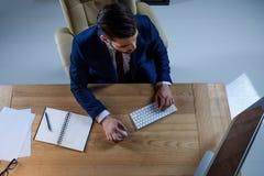 надземный взгляд бизнесмена работая на компьютере Стоковые Фотографии RF
