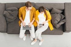 надземный взгляд молодых пар используя цифровые приборы на уютном кресле стоковые фото