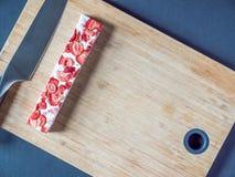 Надземный взгляд отрезал нугу клубники с ножом на деревянной доске Стоковые Фото