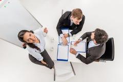 надземный взгляд усмехаясь коммерсантки смотря вверх пока коллеги имея обсуждение на встречать Стоковая Фотография RF