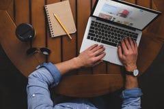надземный взгляд человека используя компьтер-книжку с вебсайтом ebay пока сидящ на таблице с кофе стоковые фото