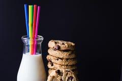 Надоите в стеклянной бутылке с печеньями солом и обломока шоколада Стоковые Фотографии RF