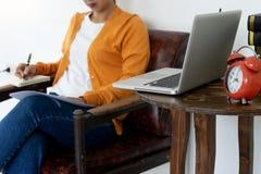 надомный труд женщины с ее компьютером и бумагой стоковые фото