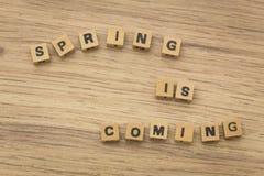 Надпись/весна аранжированный приходить/от блоков зашнурованных на строке стоковая фотография