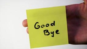Надпись до свидания на стикере на стекле Заметьте ДО СВИДАНИЯ на стекле от обиденной персоны, белой предпосылки Стоковая Фотография